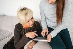 Une jeune fille explique à une femme agée comment utiliser un comprimé ou montre une certaine application ou t'enseigne comment e images stock