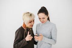 Une jeune fille explique à une femme agée comment utiliser un téléphone portable ou montre une certaine application ou enseigne c Photo stock