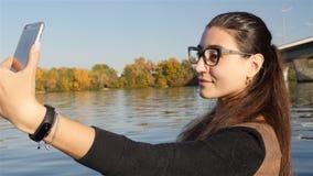 Une jeune fille fait un selfie près de l'eau Plan rapproché Mouvement lent banque de vidéos