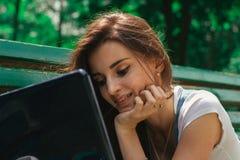 Une jeune fille gaie de portrait en gros plan avec un ordinateur portable Photo stock