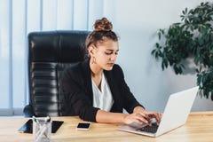 Une jeune fille habillée dans des vêtements d'affaires travaille sur un ordinateur portable Pendant le ceci elle se comporte très image libre de droits