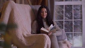 Une jeune fille lit un livre tout en se reposant dans une chaise près de l'arbre de Noël clips vidéos