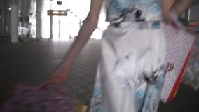 Une jeune fille marche par le tunnel avec des achats banque de vidéos