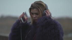 Une jeune fille met dessus des écouteurs et allume la musique banque de vidéos