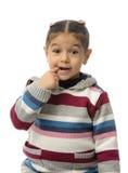Une jeune fille mordant son doigt photos stock