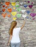Une jeune fille peint un coeur d'arc-en-ciel d'aquarelle sur le mur en pierre Images libres de droits