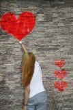 Une jeune fille peint un coeur rouge d'aquarelle sur le mur en pierre Photographie stock libre de droits