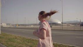 Une jeune fille pulsant pendant le début de la matinée À l'arrière-plan, équipements de sports du parc olympique de Sotchi clips vidéos