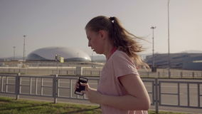 Une jeune fille pulsant pendant le début de la matinée À l'arrière-plan, équipements de sports du parc olympique de Sotchi banque de vidéos