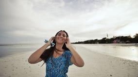Une jeune fille russe avec des émotions heureuses marche le long de la plage et pose devant l'appareil-photo La fille est clips vidéos