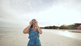 Une jeune fille russe avec des émotions heureuses marche le long de la plage et pose devant l'appareil-photo La fille est banque de vidéos