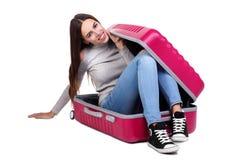 Une jeune fille s'assied dans une valise rose D'isolement sur le fond blanc Image stock