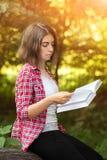 Une jeune fille s'assied dehors sur l'herbe dans un arbre lisant un livre, regard songeur, un jour d'été dehors en parc Photographie stock