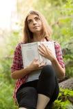 Une jeune fille s'assied dehors sur l'herbe dans un arbre lisant un livre, regard songeur, un jour d'été dehors en parc Photos libres de droits