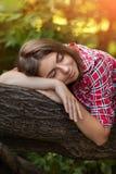 Une jeune fille s'assied dehors sur l'herbe dans un arbre, regard de couvée, un jour d'été dehors en parc Photo stock