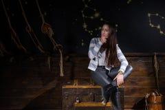 Une jeune fille s'assied sur un coffre et essayer de trouver une solution de Co photo stock