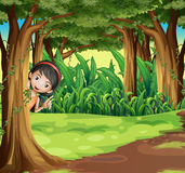 Une jeune fille se cachant à la forêt Photographie stock libre de droits