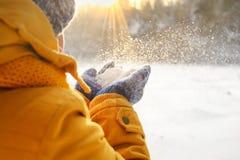 Une jeune fille se réjouit pour neiger au coucher du soleil Photographie stock