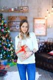 Une jeune fille se tenant avec le cadeau a attaché le ruban rouge dans le smili de mains Photos stock