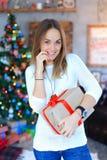 Une jeune fille se tenant avec le cadeau a attaché le ruban rouge dans le smili de mains Photographie stock libre de droits