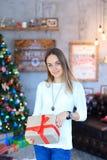 Une jeune fille se tenant avec le cadeau a attaché le ruban rouge dans le smili de mains Photos libres de droits