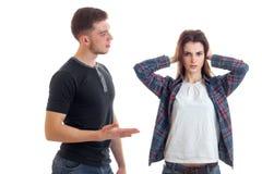 Une jeune fille se tient à côté d'un type qui lui dit quelque chose et elle a fermé des oreilles avec ses mains et regard directe Photo stock