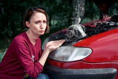 Une jeune fille se tient à une voiture cassée et tient une mauvaise pièce de rechange, un générateur électrique, ne comprend pas  photo stock