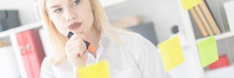Une jeune fille se tient près d'un conseil transparent avec des autocollants Elle tient une tasse et un marqueur image libre de droits