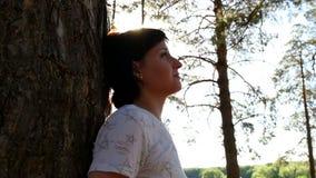 Une jeune fille se tient prêt un arbre dans une forêt le glisseur d'appareil-photo de mouvement Reposez-vous et des promenades da banque de vidéos