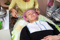 Une jeune fille se trouve sur le divan avec un chapeau rose sur ses cheveux tout en exécutant un darsonvalization sur le visage a photo stock
