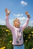 Une jeune fille sereine avec des mains a augmenté dans l'éloge. Photos libres de droits