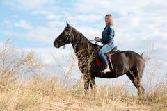 Une jeune fille sur un cheval foncé Images stock