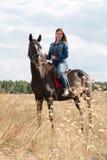 Une jeune fille sur un cheval foncé photo libre de droits