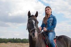 Une jeune fille sur un cheval foncé Photo stock