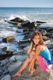 Une jeune fille sur une roche Photographie stock