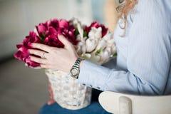 Une jeune fille tient des fleurs de ressort dans des ses mains Une fille et un bouquet de belles fleurs Image libre de droits