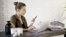 Une jeune fille tient un téléphone fonctionnant avec un ordinateur portable photo libre de droits