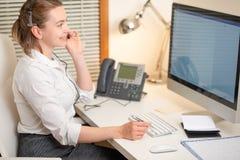 Une jeune fille travaille à un centre d'appels Pour un lieu de travail avec un téléphone Un microphone avec un microphone Service photo stock