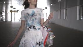 Une jeune fille va sur une transition avec des paquets banque de vidéos