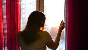Une jeune fille vient à la fenêtre et habille des écouteurs pour écouter la musique Fond brouillé avec le coucher du soleil, femm banque de vidéos