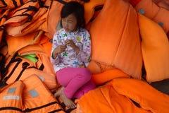 Une jeune fille vietnamienne s'asseyant dans une pile des gilets de vie oranges Photographie stock