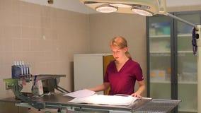 Une jeune infirmière féminine blonde prépare une table d'opération dans la clinique de vétérinaire, redresse la lampe, abaisse la banque de vidéos