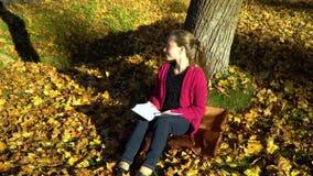 Une jeune jolie adolescente s'assied sous un arbre dans la forêt d'automne et lit un livre Elle rêve La fille est sereine et clips vidéos