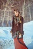 Une jeune jolie fille marche dans la forêt pendant l'hiver image stock