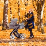 Une jeune mère avec une poussette parle à son téléphone portable tout en marchant en parc photos stock