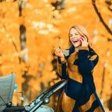 Une jeune mère avec une poussette parle à son téléphone portable tout en marchant en parc photographie stock libre de droits