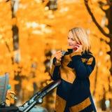Une jeune mère avec une poussette parle à son téléphone portable tout en marchant en parc photographie stock