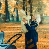 Une jeune mère avec une poussette parle à son téléphone portable tout en marchant en parc photo libre de droits