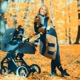 Une jeune mère avec une poussette parle à son téléphone portable tout en marchant en parc images stock