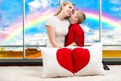 Une jeune mère avec un beau fils de bébé tenant un oreiller dans la forme du coeur sur le fond de Windows panoramique avec une pl Photo stock